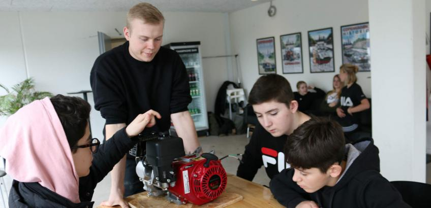 Karam, Jeppe og Arian fra 8.D øver sig i at samle en gokartmotor under kyndig vejledning af Tobias Thrane, der læser til automatiktekniker.